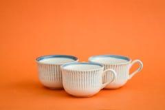 Klassieke Witte en Blauwe Koffiekoppen op Oranje Achtergrond Royalty-vrije Stock Afbeeldingen