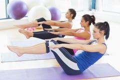 Klassificera sträckning på mats på yogagrupp i konditionstudio arkivbild