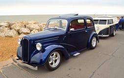 Klassiker blåa Ford Motor Car med släpet som formas som en VW-campareskåpbil som parkeras på sjösidapromenad Royaltyfri Fotografi