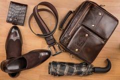 Klassische braune Schuhe, Aktenkoffer, Gurt und Regenschirm auf dem Bretterboden Lizenzfreie Stockfotos