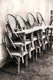 Klassische Café-geflochtene Stühle gestapelt gegen eine Wand Stockfoto