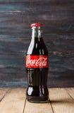 Klassische Flasche von Coca-Cola auf rustikalem Hintergrund Lizenzfreie Stockfotografie