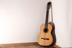 Klassische Gitarre auf hölzerner Platte und weißem Hintergrund Stockfoto