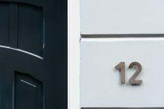 Klassische grüne Tür mit Nr. 12 Abbildung der roten Lilie Lizenzfreies Stockfoto