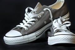Klassische Jugendfußbekleidung der grauen Turnschuhe Stockfotos