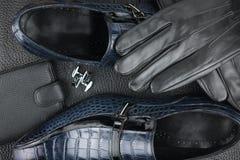 Klassische Männer ` s Schuhe, Manschettenknöpfe, Handschuhe und Geldbeutel auf dem schwarzen Leder Lizenzfreie Stockfotos