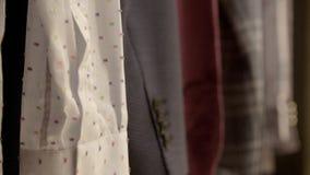 Klassische männliche Hemden, die an der Kleidungs-Schiene hängen stock video footage