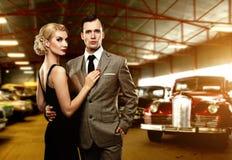 Klassische Paare gegen Retro Autos Stockfoto