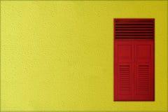 Klassische rote hölzerne Fenster auf gelbem rauem Zementhintergrund Lizenzfreies Stockbild