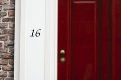 Klassische rote Tür mit Nr. 16 Abbildung der roten Lilie Lizenzfreie Stockfotos
