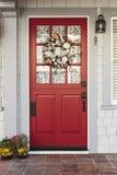 Klassische rote Tür zu einem weißen Haus stockbilder