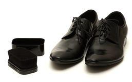 Klassische Schuhe der schwarzen Männer mit Schwamm auf Weiß lizenzfreies stockfoto