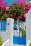 Klassische Straße mit bunten Blumen in Santorini Stockfotografie