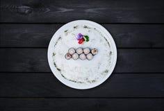 Klassische Sushirolle mit Garnele auf einer weißen Ronde, verziert mit kleinen Blumen, japanisches Lebensmittel, Draufsicht schwa Lizenzfreies Stockfoto