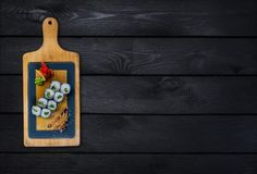 Klassische Sushirolle mit Gurke auf einem hölzernen Brett Beschneidungspfad eingeschlossen Schwarzer hölzerner Hintergrund Lizenzfreie Stockfotos