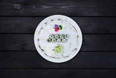 Klassische Sushirolle mit Gurke auf einer weißen Ronde, verziert mit kleinen Blumen, japanisches Lebensmittel, Draufsicht schwarz Lizenzfreie Stockfotos
