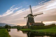Klassische Szene einer niederländischen Windmühle und des Hauses nahe einem Kanal mit einem großen Himmel als Hintergrund stockfotos