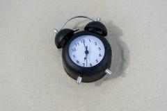 Klassische Uhr auf dem Sand Stockfotos