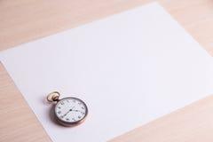 Klassische Uhr auf einem weißen Blatt Papier Stockbilder