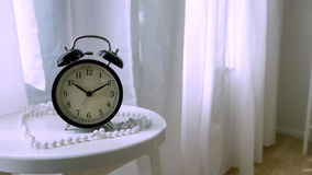 Klassische Uhr auf weißer Tabelle im Schlafzimmer Lizenzfreies Stockfoto