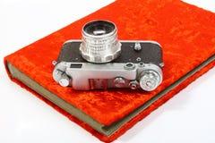 Weinlesefilmkamera, die auf einem hellen roten alten photoalbum liegt Stockbild