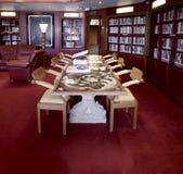 Klassischer Bibliotheksraum mit Ledersesseln, Steintabelle und Weltatlas Lizenzfreie Stockfotografie