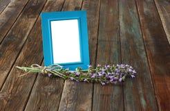 Klassischer blauer Bilderrahmen auf Holztisch und Salbei pflanzen Dekoration. Stockfotos