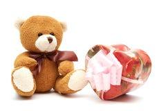Klassischer brauner Teddy Bear mit Herz-förmigem Geschenk lizenzfreies stockbild