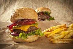 Klassischer deluxer Cheeseburger mit Kopfsalat, Zwiebeln, Tomate und Essiggurken auf einem Samenbrötchen des indischen Sesams Stockfotografie