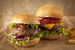 Klassischer deluxer Cheeseburger mit Kopfsalat, Zwiebeln, Tomate und Essiggurken auf einem Samenbrötchen des indischen Sesams Lizenzfreies Stockfoto