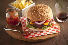 Klassischer deluxer Cheeseburger mit Kopfsalat, Zwiebeln, Tomate und Essiggurken auf einem Samenbrötchen des indischen Sesams Lizenzfreie Stockfotos