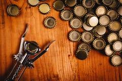 Klassischer Flaschenöffner und Stapel von Bierflaschekappen Stockbild