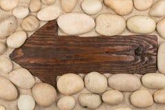 Klassischer hölzerner Pfeil und weiße Steine auf dem Sand Stockbild