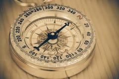 Klassischer Kompass auf einem hölzernen Stockbild