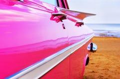 Klassischer rosafarbener Cadillac am Strand Lizenzfreie Stockfotos