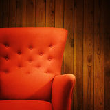 Klassischer roter Lehnsessel nahe einer hölzernen Wand Stockfotografie