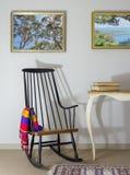 Klassischer Schaukelstuhl und zwei alte Bücher auf im altem Stil Weinlesetabelle und zwei hingen Malereien mit Beschneidungspfad  Stockbilder