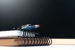 Klassischer Staffelungsschulhintergrund mit Bildungsausrüstungsstift, -bleistift, -buch und -rückenbrett mit Kopienraum stockbilder