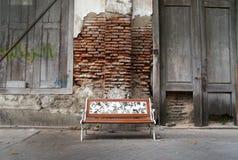 Klassischer Stuhl, alte Backsteinmauer und alte Holztür Stockbild