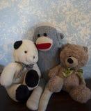 Klassischer Teddy Bears gegen eine blaue Wand mit Socke-Affe-Freund Stockfoto