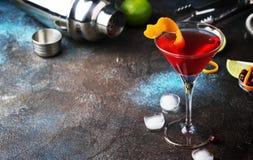 Klassisches alkoholisches Cocktail kosmopolitisch mit Wodka, Likör, Preiselbeersaft, Kalk, Eis und orange Eifer, dunkler Barzähle lizenzfreies stockbild