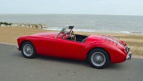 Klassisches Auto des Rot-MGA parkte auf Seeseitepromenade mit Meer im Hintergrund Stockbild