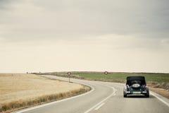 Klassisches Auto in einer Land-Straße Lizenzfreie Stockfotografie