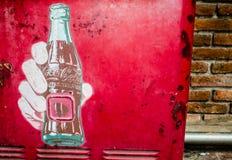 Klassisches Brandinglogo des eingetragenen Warenzeichens von Coca-Cola mit der Karikaturart der Mannhand eine Flasche auf roter r Lizenzfreies Stockbild