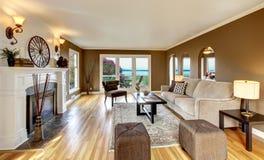 Klassisches braunes Wohnzimmer mit weißem Kamin. Lizenzfreies Stockbild