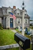 Klassisches Cape Cod-Haus mit Sternenbanner Stockbild