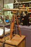Klassisches Designteleskop mit Holzbeinunterstützung in einem Shop, der Weinlesewaren verkauft Stockbilder