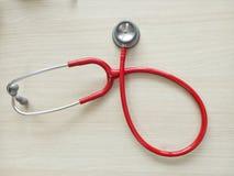 klassisches einzelnes rotes Stethoskop, lokalisiert auf hölzernem Hintergrund Stockfoto