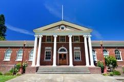 Klassisches Gebäude des roten Backsteins mit griechischem weißem Spalten-Eingang Lizenzfreie Stockfotografie