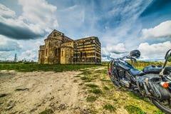 Klassisches Motorrad durch eine kleine Kirche in Sardinien Stockfotografie